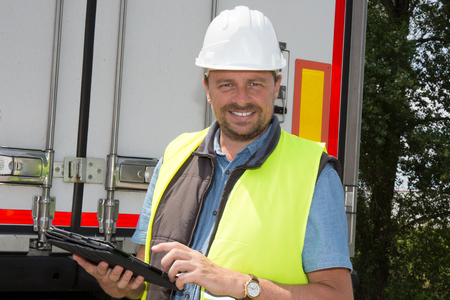 logging truck: Male contractor using tablet PC while standing by logging truck