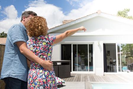 coppia che si abbraccia davanti alla nuova casa moderna, vista posteriore esterna di nuovo guardare la loro casa dei sogni Archivio Fotografico