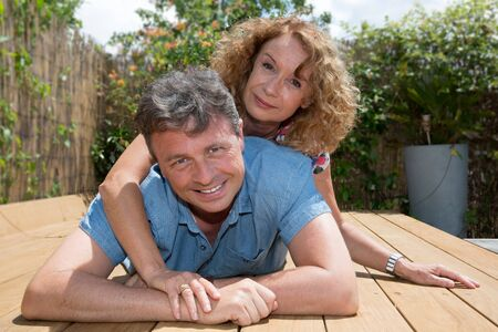 Lovers outside spend good time in the garden, mid aged couple Stock Photo