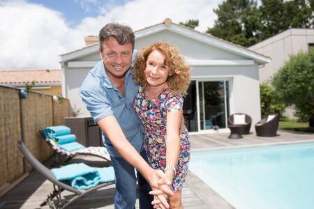 forties: Happy couple sitting in from of their new home with swimming pool Stock Photo