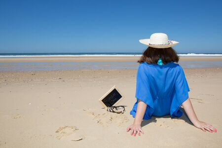 Beach vacation, young woman in sunhat and sitting enjoying looking view of beach ocean on hot summer day.