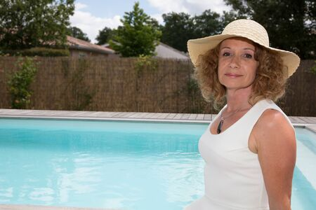 suncare: Middle aged sexy woman in the pool with a hat and white dress Stock Photo