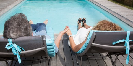 pool side: A happy couple on pool side chairs having fun Stock Photo