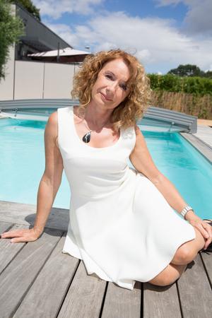 Retrato de una mujer de mediana edad sonriente relajante por piscina Foto de archivo - 60640026