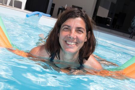 fun activity: Smiling portrait of pretty woman in swimming pool. Stock Photo