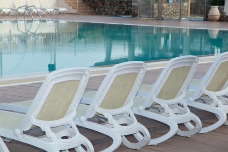lounge chairs: Lounge chairs by the pool on summer Stock Photo
