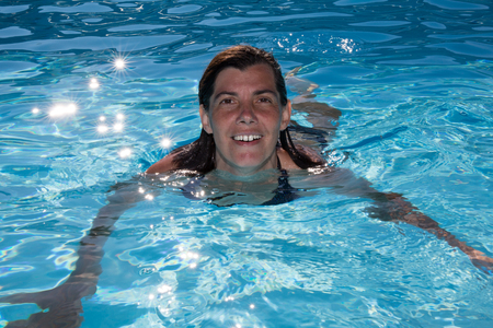 Cheerful and smiling woman in swimming-pool Banque d'images