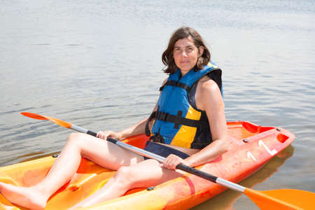 adventuring: Fit woman rowing on lake in a kayak and smiling