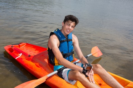 adventuring: Happy young man rowing on lake in kayak and smiling Stock Photo