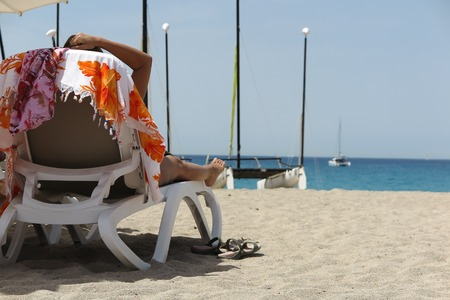 caribe: Woman relaxing in long chair by the beach