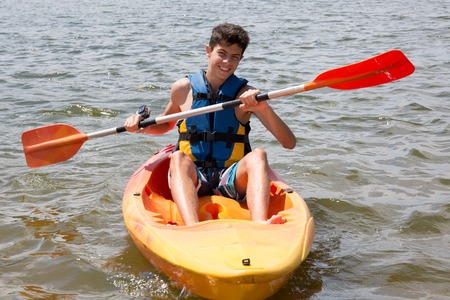 Happy young man rowing on lake in a kayak and smiling Stock Photo