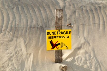 sea oats: Beach Dunes and wooden picket fence, with sign warning Do Not Walk On Dunesin french Stock Photo