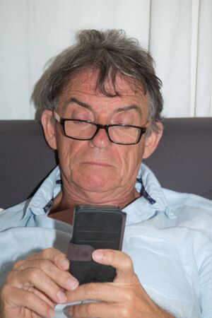 inseparable: A senior using successfully his inseparable smartphone