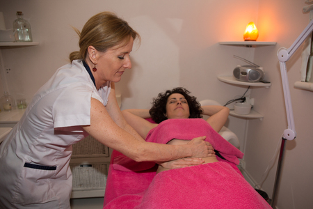 Woman having stomach massage. Body care at beauty center