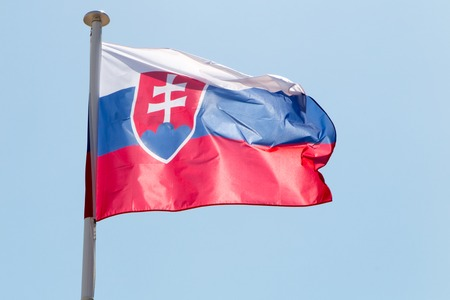 central european: Flag of Slovakia waving in the wind under blue sky