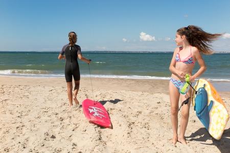 appreciating: Caucasian girls playing surf under blue sky