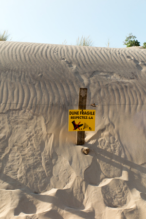 Beach Dunes and wooden picket fence, with sign warning Do Not Walk On Dunesin french Stock Photo