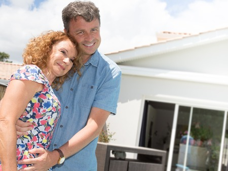 realestate: Happy couple standing in front of house under construction