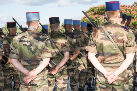 camoflauge: Military men at a parad under blue sky