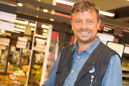 shop assistant: Shop assistant in a supermarket at the vegetable shelf Stock Photo