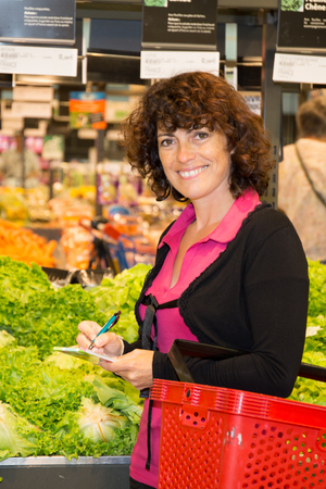 green leafy vegetables: Closeup portrait of a woman picking up, choosing green leafy vegetables in grocery store