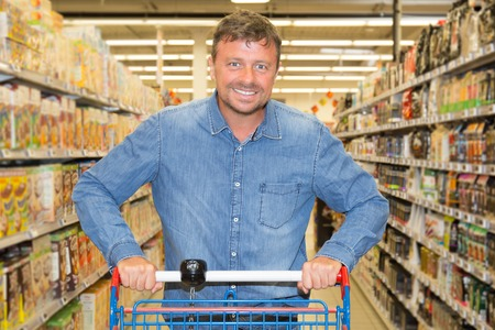 Man driving shopping cart while grocery shopping in supermarket