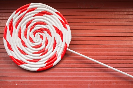 lolli: a red and white large spiral on the wooden table
