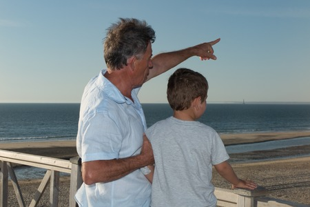 grand son: Father or grand father and his little son pointing at something with finger.
