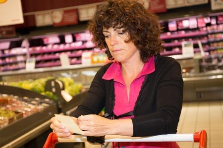 receipt: Thoughtful Brunette woman holding receipt in supermarket