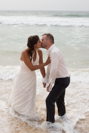 trash the dress: Newlyweds sharing a romantic moment at the beach kissing