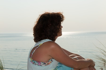 beachfront: Lonely Woman in Casual Outfit with Black Hair Sitting at Beachfront on Sunny Day.