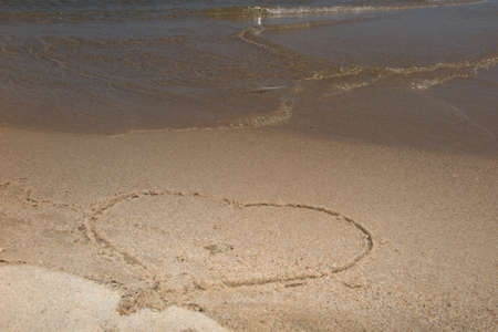 evoking: Heart drawing in the sand . The ocean waves gently wash away part of the heart