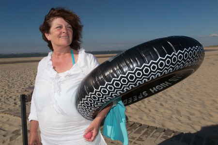 beach buoy: Woman smiling at the beach smiling with an inflatable buoy Stock Photo