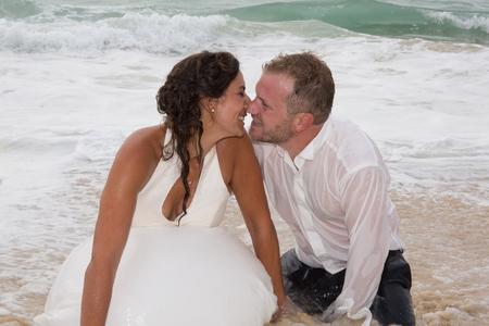 besos apasionados: Romantic newly-married couple enjoying a summer vacation. Young groom kissing his bride in sea Foto de archivo