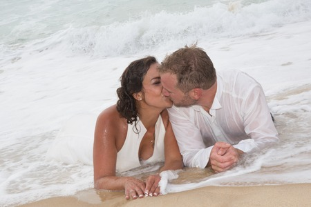 kissing mouth: loving groom kissing brides mouth on beach