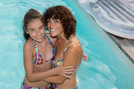 mum and daughter: Smiling beautiful woman and young girl bathes in pool