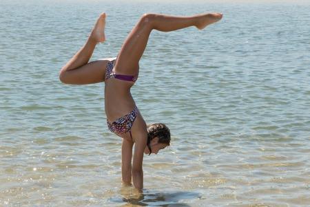 Happy young woman doing cartwheel on the beach bikini