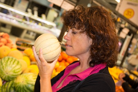 Woman with child choosing melon fruit during shopping at supermarket