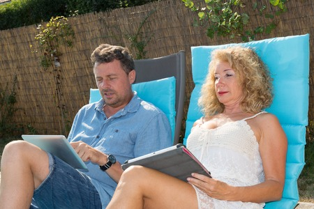 thalasso: Happy couple resting in deck chairs by pool with tablet Stock Photo