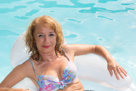 midlife: summer vacations image with adult midlife woman relaxing in a beautiful lake
