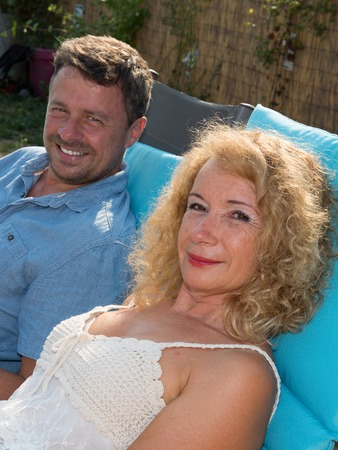 Happy couple resting in deck chairs by the pool at summer