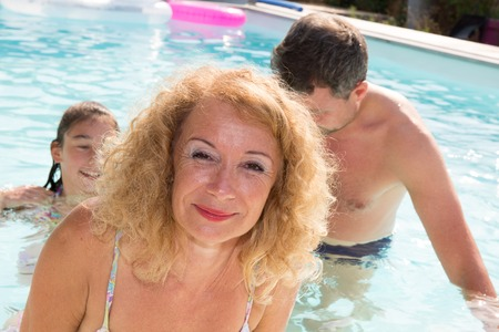Happy and lovely family at the pool having fun