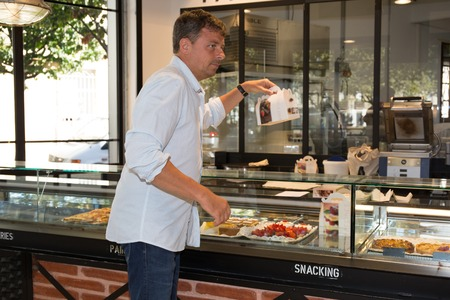 Handsome man buying some cookies and cakes in a pastry shop