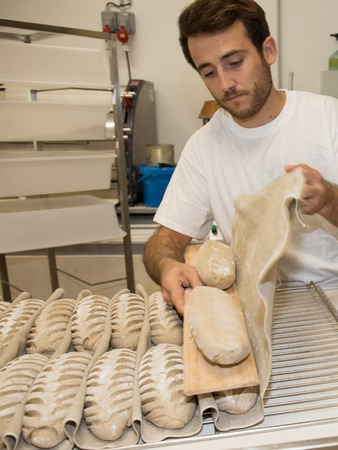 processed grains: Baker putting unbaked bread dough into the hot oven in a bakery