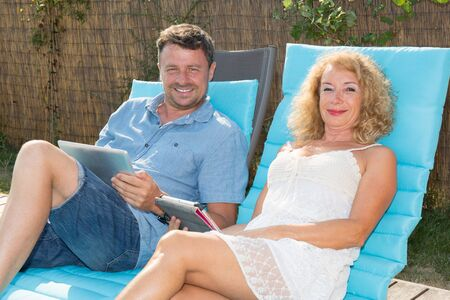 Happy couple resting in deck chairs by pool with tablet Banque d'images