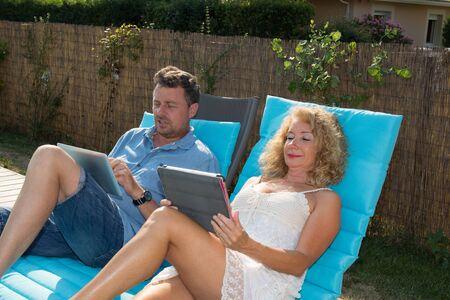 thalasso: Heureux couple de repos dans les chaises longues de la piscine avec la tablette Banque d'images