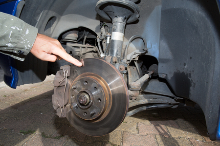 impact wrench: Man changing a wheel of modern car in a workshop