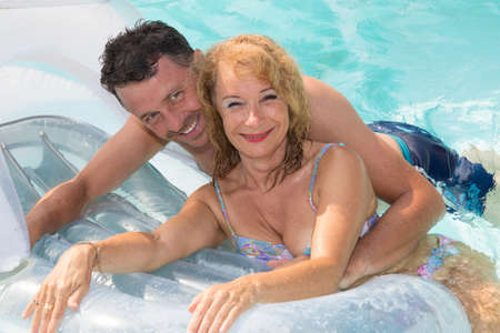 midlife: Cheerful midlife couple on holiday in swimming Pool
