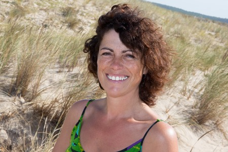 40 year old woman: Portrait of smiling 40-year-old brunette woman at the beach