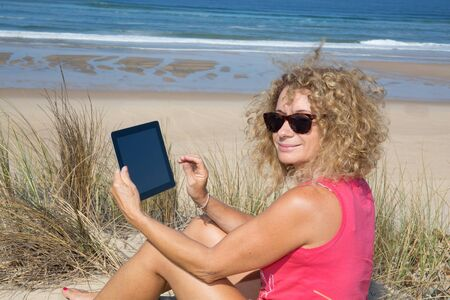 Blond woman using electronic tablet at the beach